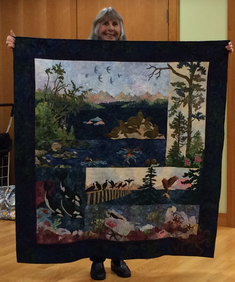 Linda C. holds the McKenna Ryan quilt she and her daughter worked on for 8 years!