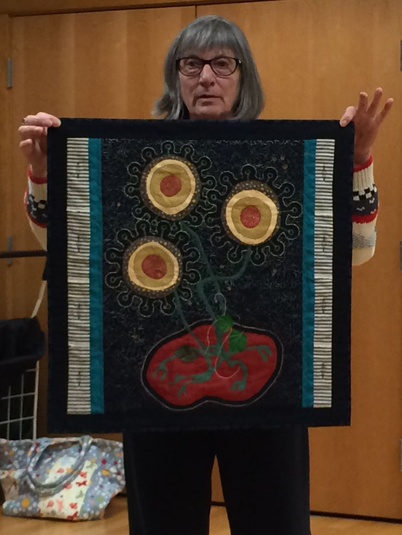 Rommie holds the quilt she started in a Jane Sasseman class.