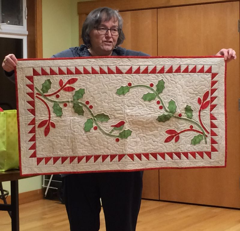 Val holds a Christmas quilt that will sit by her fireplace.