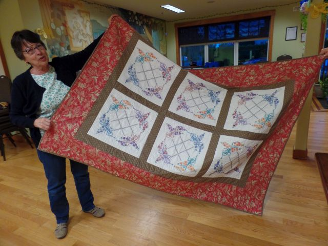 Judy K. shows her embroidered quilt top.